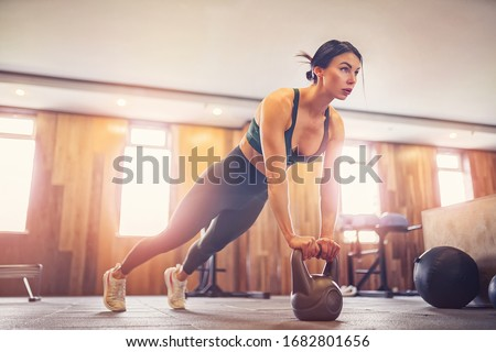 young motivated girl doing plank exercise using kettlebells at gym, full length photo, copy space.
