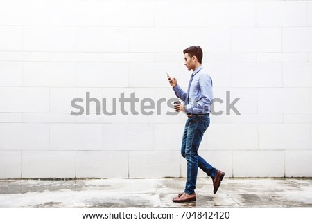 Young motivation Businessman Text or Reading Smart Phone while Walk outdoor building, Lifestyle of modern male, Technology to Communicate in Business concept