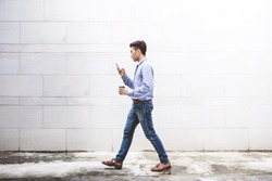 Young motivation Businessman use smart phone while walk outdoor building, Lifestyle of modern male to communicate, message or technology in business concept