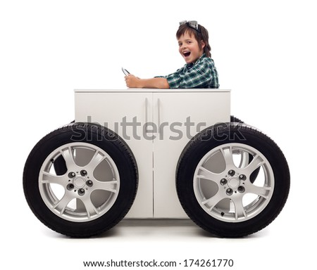 Young motorist - boy playing with car tires attached to wooden box