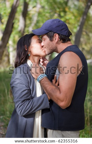 Young multi cultural couple kissing in fall forest