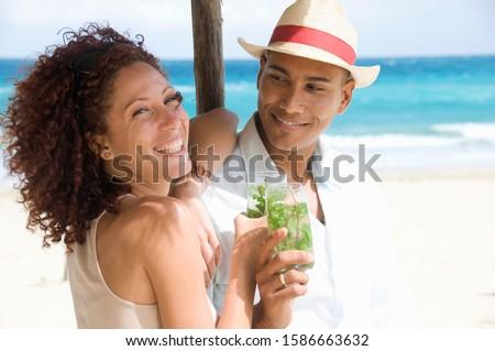 Young multi-ethnic couple enjoying drinks on the beach in Havana, Cuba