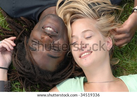 young multi-ethnic couple lying in the garden