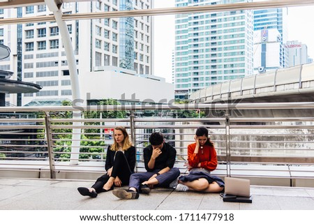 Young multi-ethnic employees are sitting sad, anxious and stressed along the sidewalk on the Sky walk. The concept of being dismissed and fired