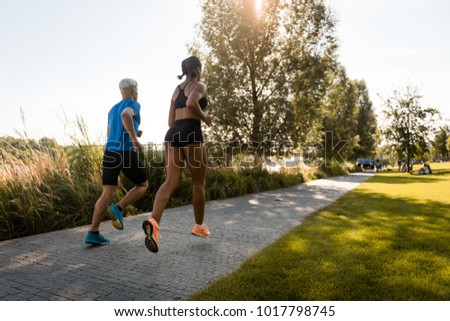 Young multi ethnic joggers running together in park #1017798745