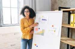 Young multi-ethnic woman with an afro hairstyle points on flip chart, looks away and explains something to the audience. Teacher, coach, mentor