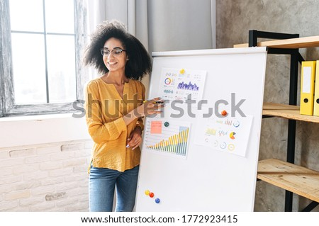 Young multi-ethnic woman with an afro hairstyle points on flip chart, looks away and explains something to the audience. Teacher, coach, mentor Stock foto ©