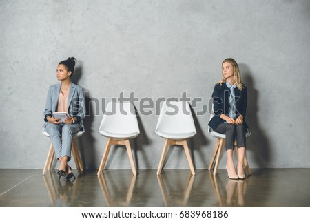 young multicultural businesswomen sitting on chairs and waiting for job interview