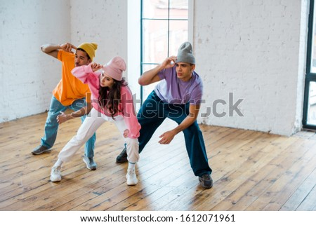 young multicultural dancers touching hats while breakdancing