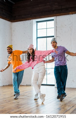 young multicultural dancers with outstretched hands breakdancing