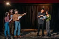young multiethnic actors and actresses rehearsing with mature theater director on stage