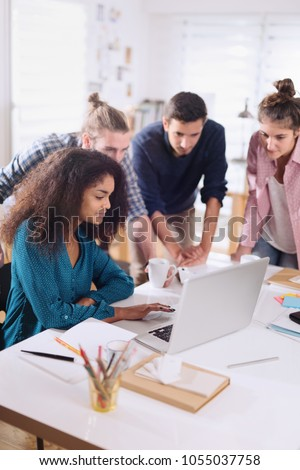 Young multiethnic business team sharing ideas on a project around a computer in a modern office