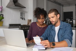 Young multiethnic couple checking bills while managing accounts on home banking app. Serious casual man and girl using laptop while looking at invoice and plan the budget to save.