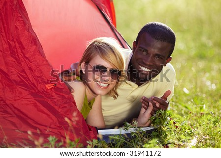 young multiethnic couple lying in tent and holding hands.
