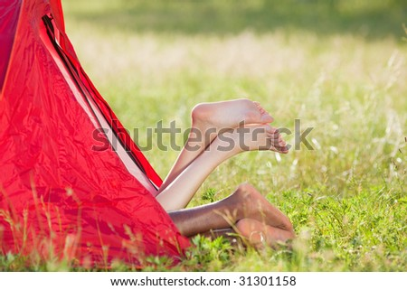 young multiethnic couple lying in tent with feet crossed. Copy space