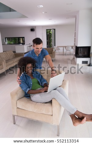 Young multiethnic couple sitting on an armchair in the luxury living room, using a laptop computer