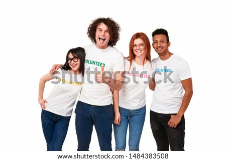 Young multiethnic friends in volunteer T-shirts cheerfully smiling and looking at camera while participating in charity movement against white background