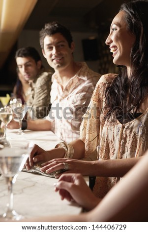 Young multiethnic group at the bar with cocktail glasses