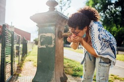 young multiethnic woman refreshing at fountain - Diverse female in hot summer drinking water at fountain outdoors - refreshment, thirsty, refreshing concept