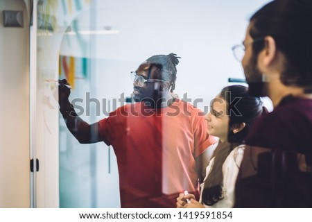 Young multiethnic women and men writing on glass board in modern office with sticky notes while creating plan of new project