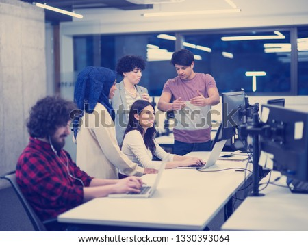 young multiethnics business team of software developers working together using laptop and desktop computers while writing programming code at modern startup office
