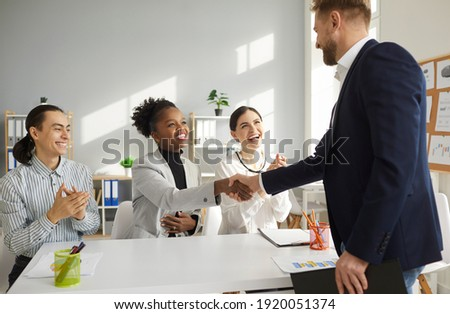 Young multiracial business team shakes hands with a man welcoming him as a new team member. Dark skinned woman congratulates her partner on a successful deal. Concept of business relations. Foto stock ©
