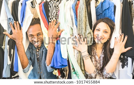 Young multiracial couple having fun at clothing flea market - Best friends sharing time shopping on cheap sale - Lovers enjoying everyday life moments - Wardrobe fashion shop concept with happy people