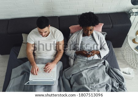 Young multiracial couple using their mobile electronic devices in bed. Internet addiction.