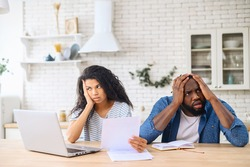 Young multiracial family argued about their budget, stressful family couple have debt problems, not able to pay their loan, manage domestic budget, study paper documents, sitting in modern apartment