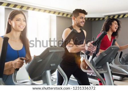 Young multiracial people exercising on cross-trainer machine in modern sport gym