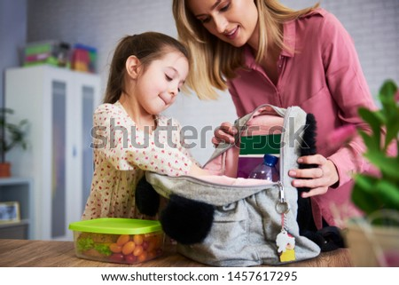 Young mum and daughter packing backpack for the school #1457617295