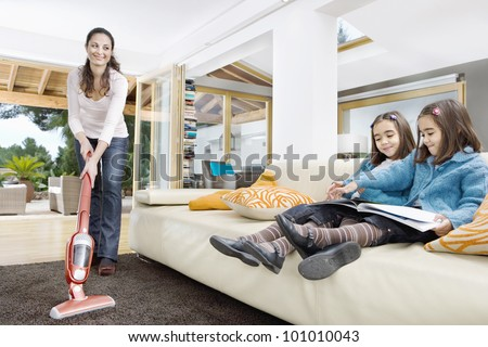 Young mum using a vacuum cleaner while her two twin daughters look at a book in the living room.