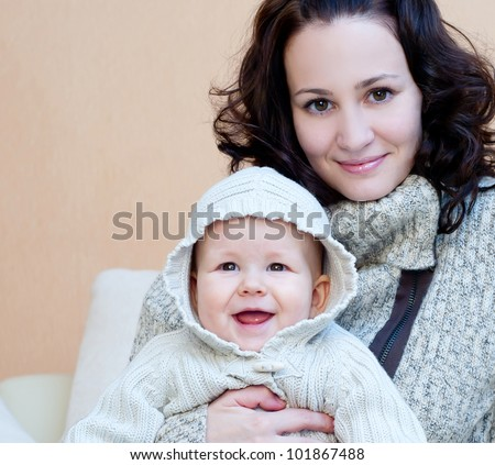 young mum with a small son in a room interior