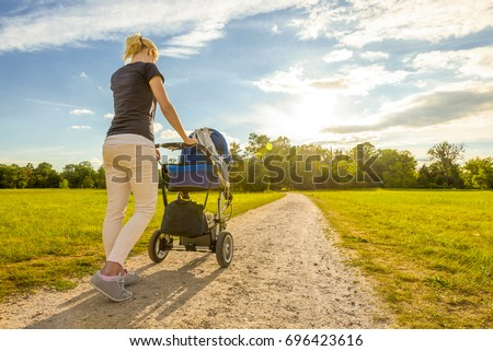 Young mummy carries a baby buggy in the beautiful royal gardens of Lednice–Valtice Cultural Landscape, South Moravia, Czech Republic #696423616