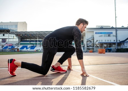 6d000c2729922c young muscular athlete at start position on race track in stadium