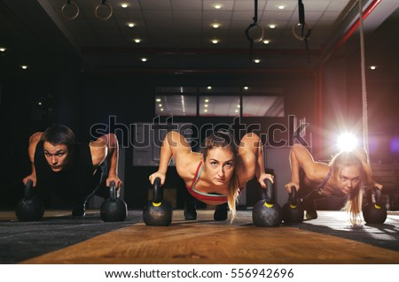 Young muscular athletes doing push up exercise with kettle bell equipment. Weightlifting, power lifting workout. Fitness, sports concept. #556942696