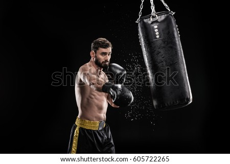Young muscular boxer exercising with punching bag  isolated on black Stock photo ©