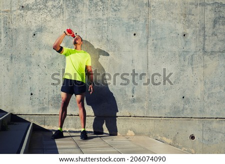 Young muscular build man with running armband on the arm drinking water of bottle, attractive athlete resting after workout outdoors, fitness and healthy lifestyle concept