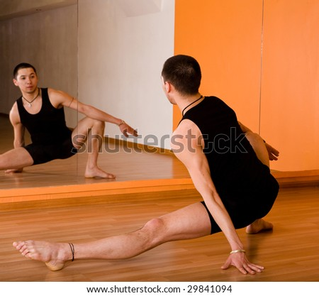 Young muscular dancer posing in dance hall