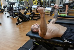 Young muscular fitness man trains pectoral muscles while lying on a bench with dumbbells in his arms at the gym