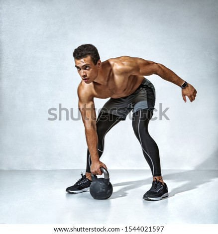 Young muscular guy training with kettlebell. Photo of handsome man with naked torso on grey background. Strength and motivation