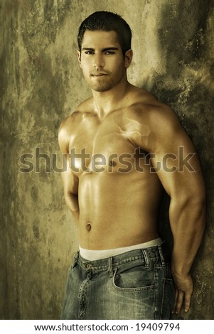 Young muscular male against wall with golden light