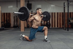 Young muscular male bodybuilder doing lunges with a barbell on his shoulders in a modern health club. Bodybuilding and Fitness