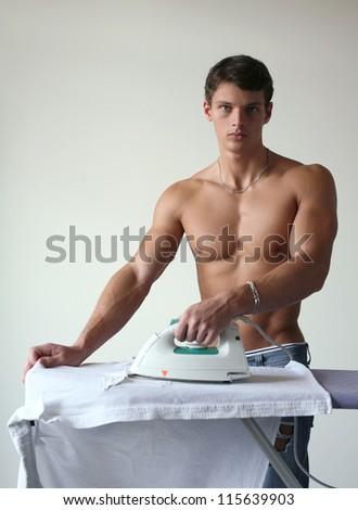 Young muscular man ironing a shirt