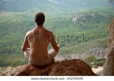 Young muscular man meditating on rock