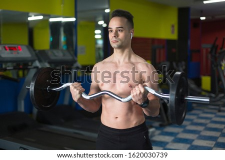 Young muscular man performing exercise with weights for biceps, inside a gym.