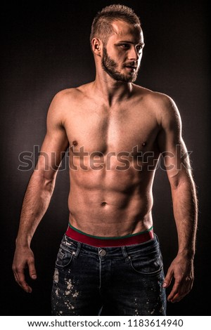 Young muscular man shows his muscles and toned torso.Studio photo sessin,potrait with the black background.He has short hair and short beard.Fitness.