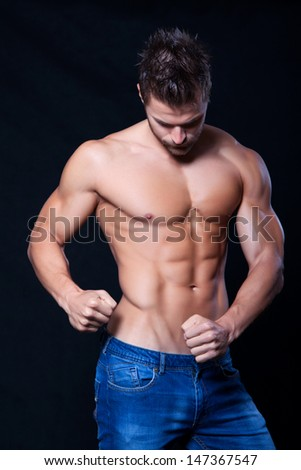 Young muscular man undressed to the waist showing his muscles on black background
