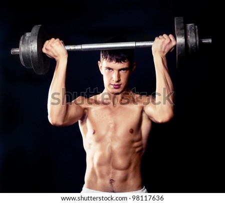 young muscular man with a bar, isolated on black studio background