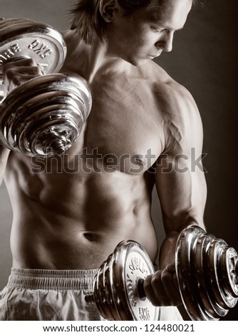 Young muscular man with dumbbells on black background